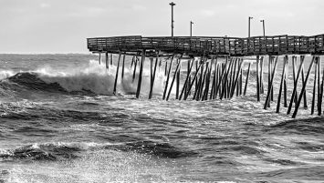 Wave crashing into an icy Avalon Pier