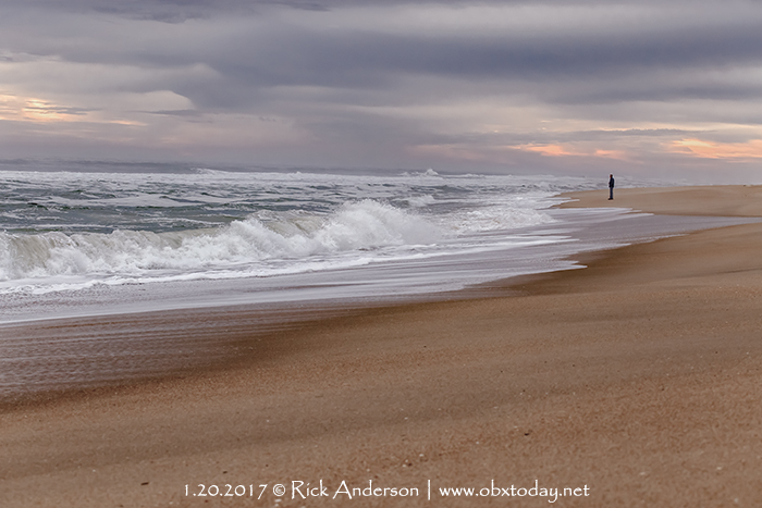 Lone person standing by the ocean at sunrise.